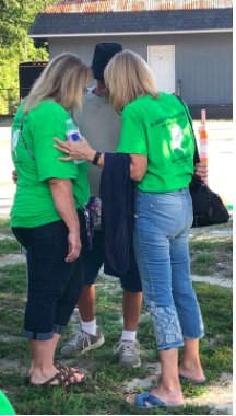 Michelle Folkenroth (left) and Holy Gieple (right) pray with a homeless man. The man had approached the sisters asking for someone to pray with and the pair happily prayed with him.